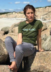 elena the massage therapist on a rock on the beach