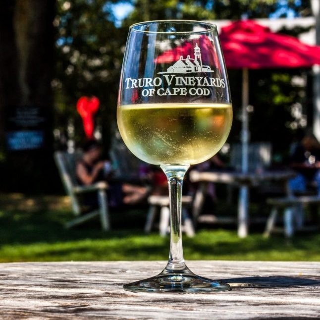 A glass of white wine in a Truro Vineyards glass