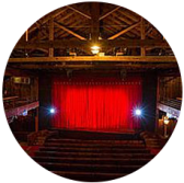 The playhouse has a red curtain closed with plenty of open seating