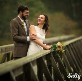 A couple on their wedding day posing on a boardwalk