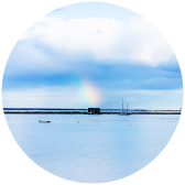 An oyster barge in Provincetown with a rainbow a top it