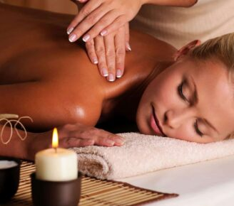 A woman gets a massage by candle light