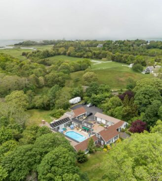 Aerial view of the inn with trees and water in the background