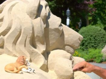 Sand sculpture of lion and man's hand by lamb being sculptured