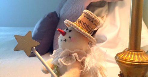 A stuffed snowman on the pillow