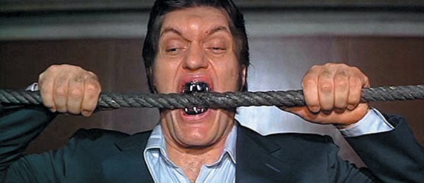 man with wicked looking teeth biting cable