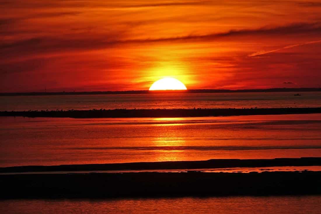 The sun sets over a beach